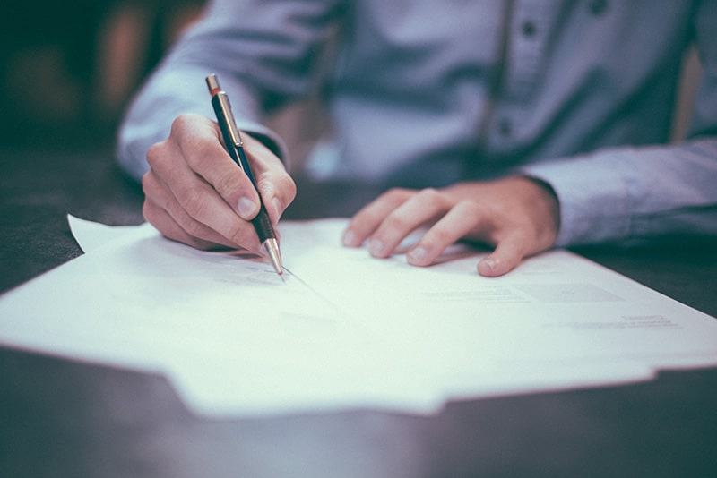 Man sitting at a desk with pen and paper planning an estate
