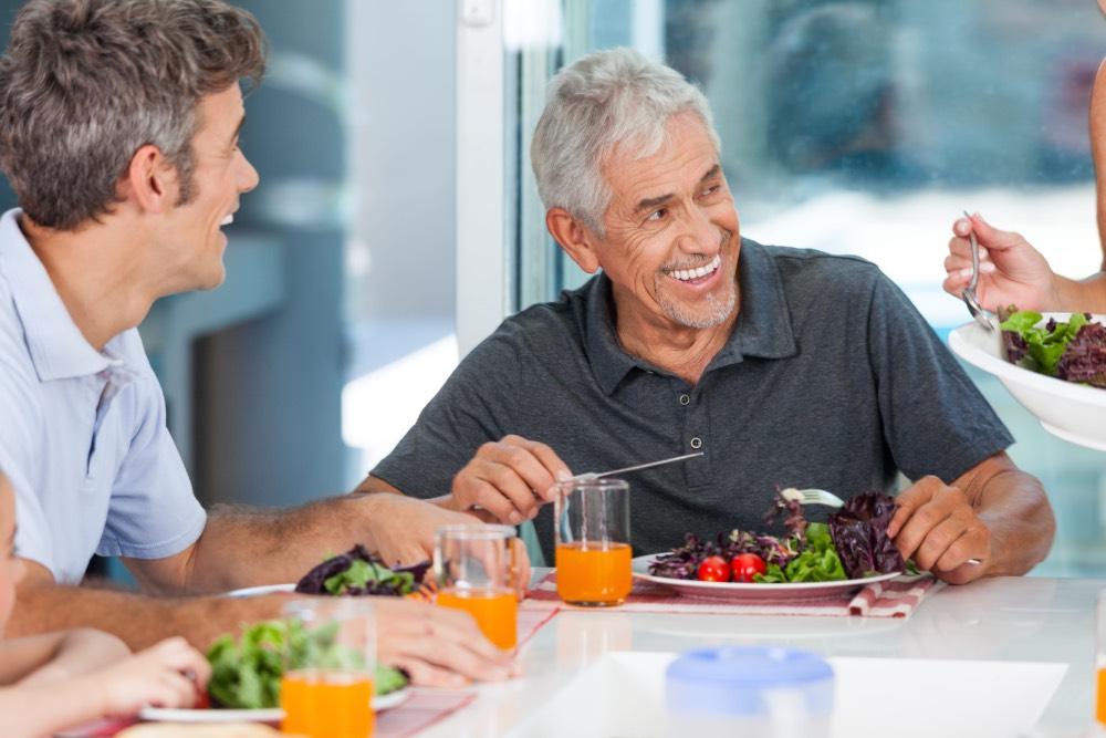 Older men eating healthy vegetables and drinking juice.